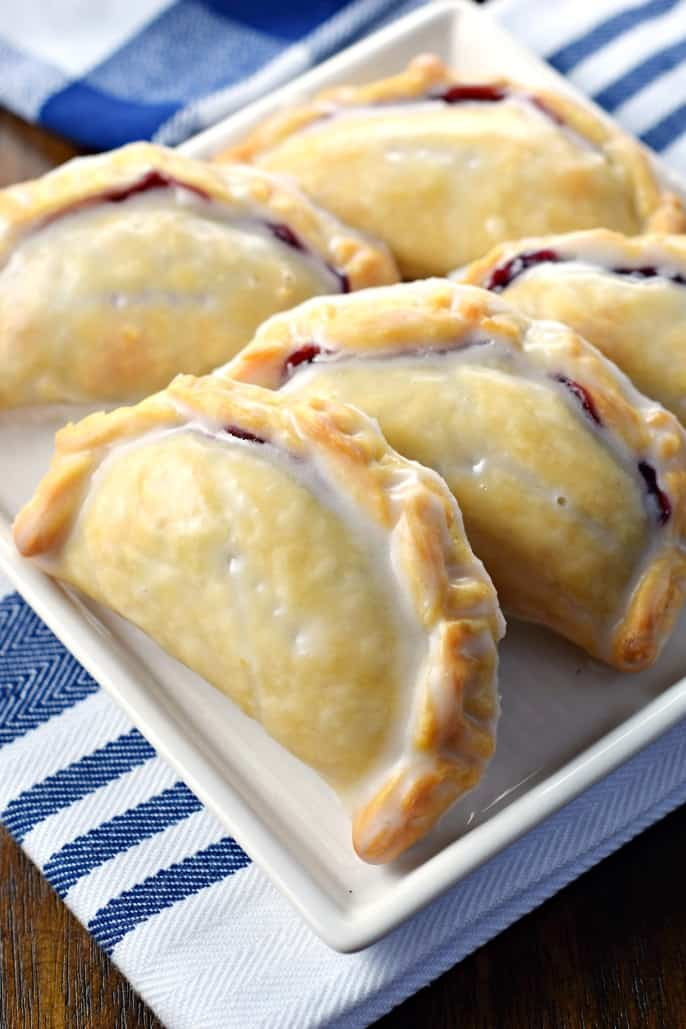 Blueberry Hand Pies lined up on a square white dessert plate.