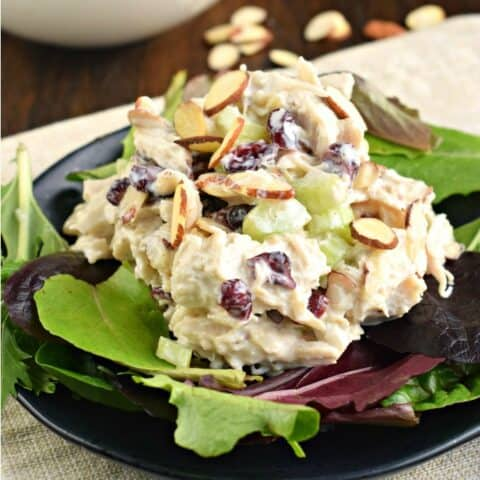 Chicken salad on plate of greens with slivered almonds.