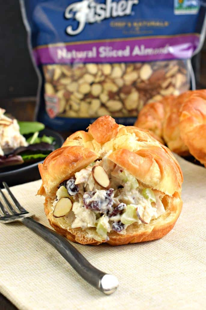 Chicken salad on croissant with Fisher almonds bag in background.