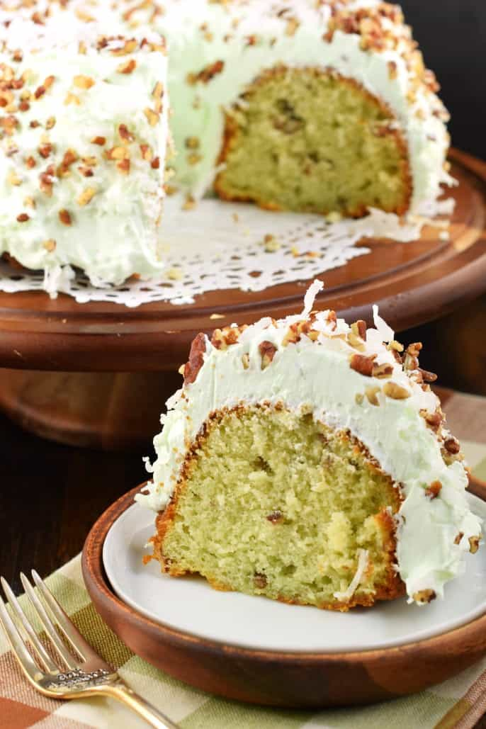 Slice of pistachio cake with pistachio frosting on a white plate with whole cake in background.