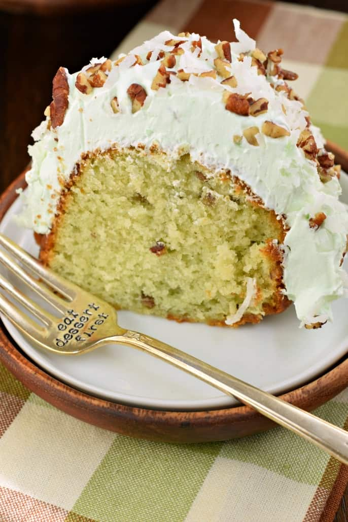 "Slice of pistachio cake with pistachio frosting on a white plate and fork that says ""eat dessert first."""