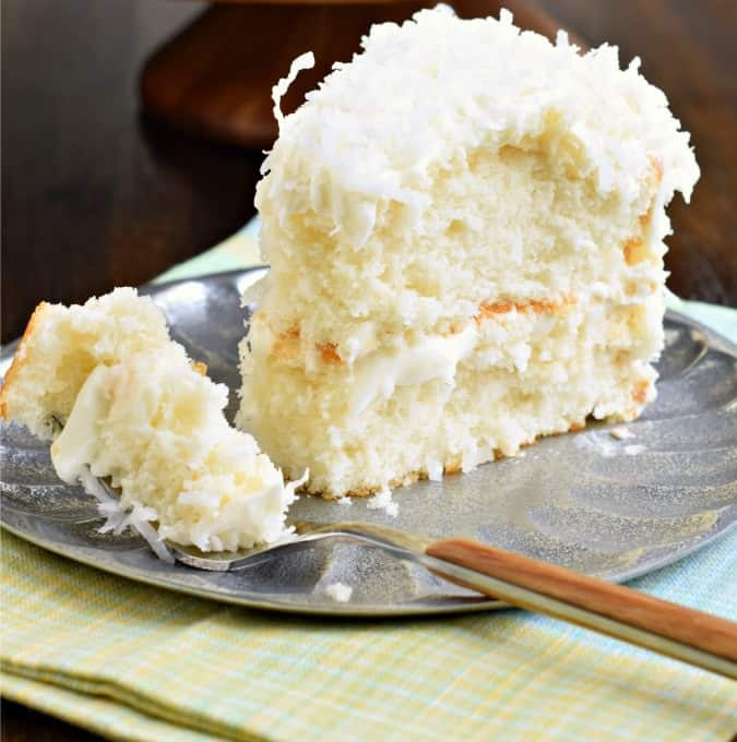 Slice of coconut cake on a silver plate with one forkful taken away.