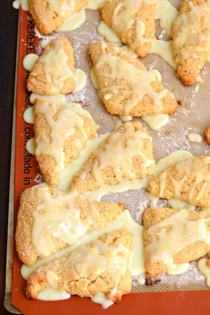 Silpat on a baking sheet topped with lemon scones and drizzled with lemon glaze.