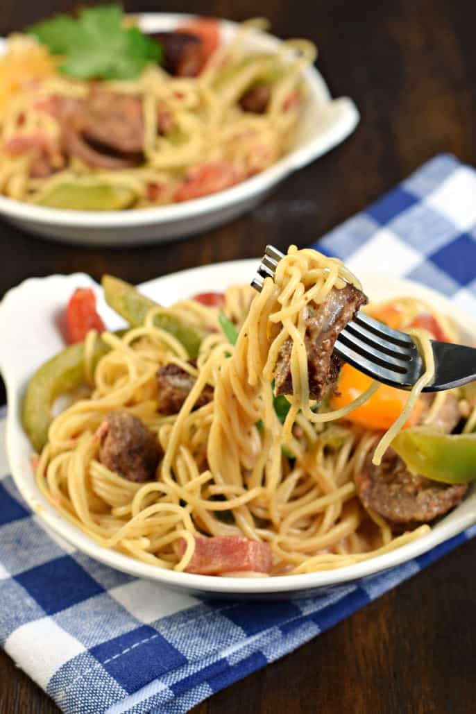 Forkful of cajun sausage pasta and peppers.
