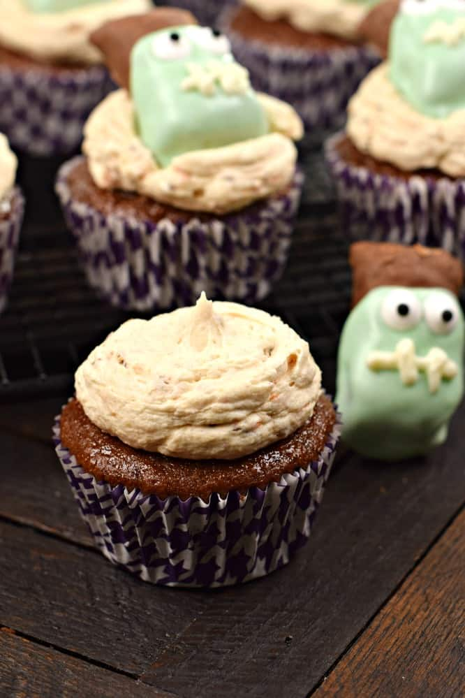 Undecorated chocolate cupcake with butterfinger frosting. Candy frankensteins in background.