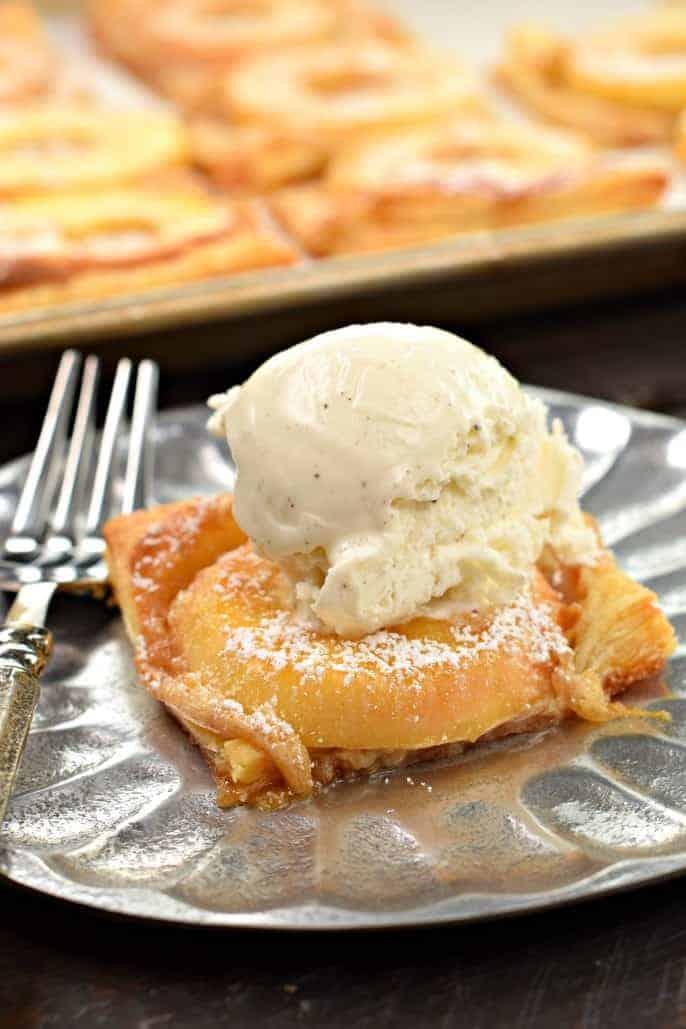 Slice of apple tart with vanilla bean ice cream.
