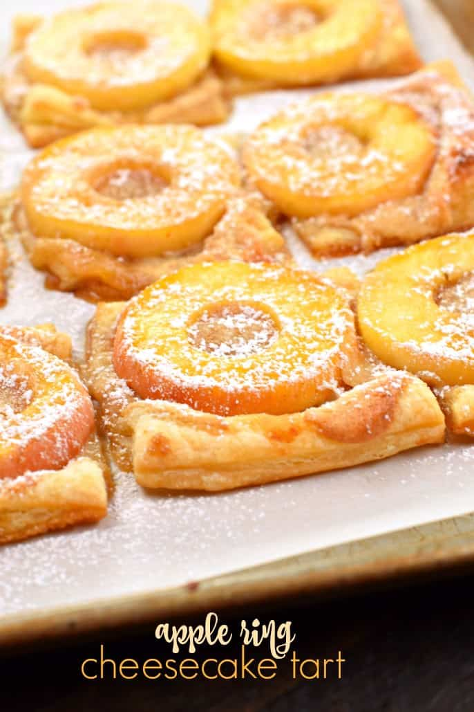 Apple tart with dough, apple rings, and powdered sugar.