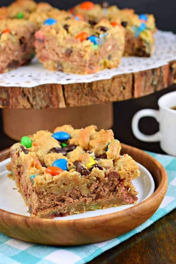 These Monster Cookie Cheesecake Bars are two layers of cookie dough packed with peanut butter and M&M'S candy and filled with a creamy chocolate cheesecake filling! #cookiedough #cheesecake #dessert