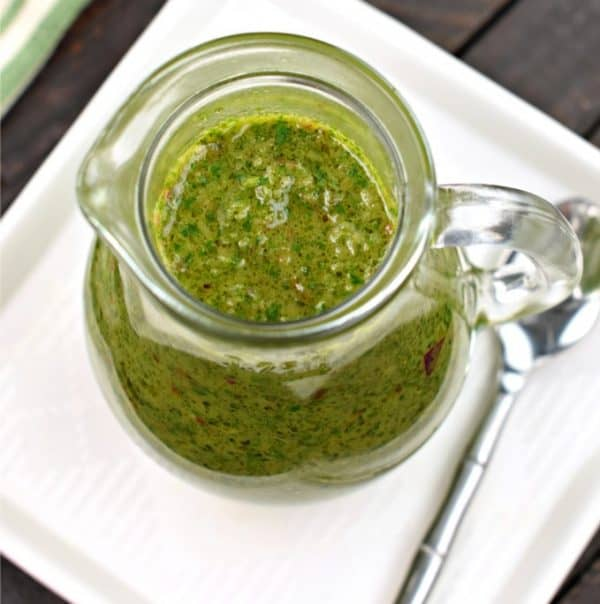 Fresh green chimichurri sauce in clear glass pitcher with spoon, vibrant, chimichurri, tex mex