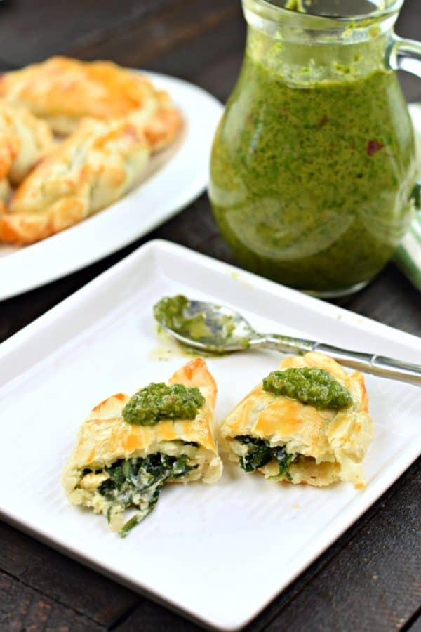 Fresh green chimichurri sauce spooned on top of spinach and cheese empanadas