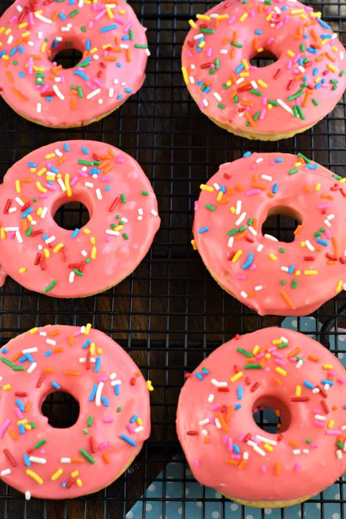 Six cherry frosted donuts on a black wire rack.
