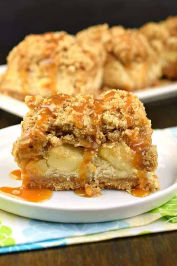 One bite of these Caramel Apple Cheesecake Bars will leave you wanting another! Cookie crust with creamy cheesecake filling, fresh apples, and a thick brown sugar streusel, all topped with a drizzle of decadent caramel sauce! #caramel #apple #cheesecake