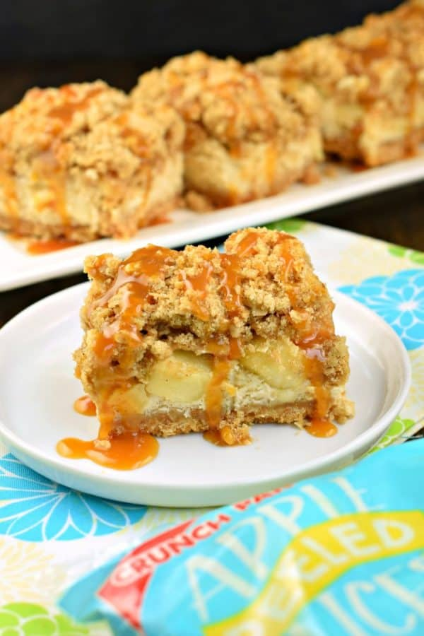 One bite of these Caramel Apple Cheesecake Bars will leave you wanting another! Cookie crust with creamy cheesecake filling, fresh apples, and a thick brown sugar streusel, all topped with a drizzle of decadent caramel sauce! #dessert #caramelapple #cheesecakebars