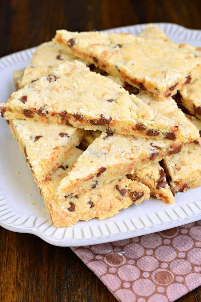 Shortbread cookies with toffee and chocolate chips cut into triangles and served on a white plate.