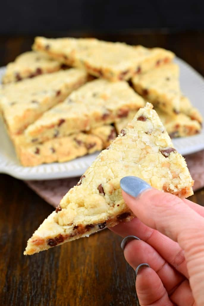 Chocolate chip shortbread with toffee bits cut into triangles and being held up.