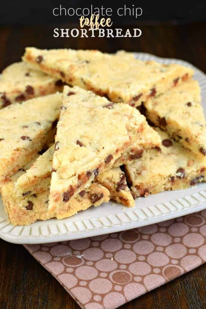 White plate on a brown linen with toffee chocolate chip shortbread cookies cut into triangles.