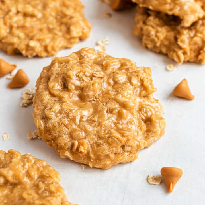 No bake oatmeal butterscotch cookies stacked on white parchment paper.