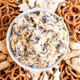 Peanut butter cookie dough dip in a bowl served with pretzels and animal crackers.