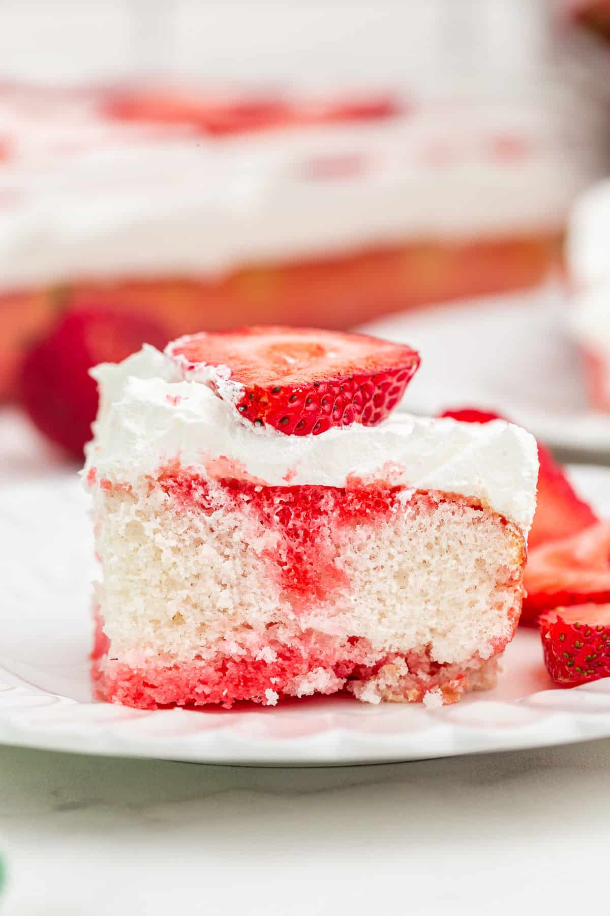 Slice of strawberry jello cake topped with whipped cream and fresh strawberries on a white plate.