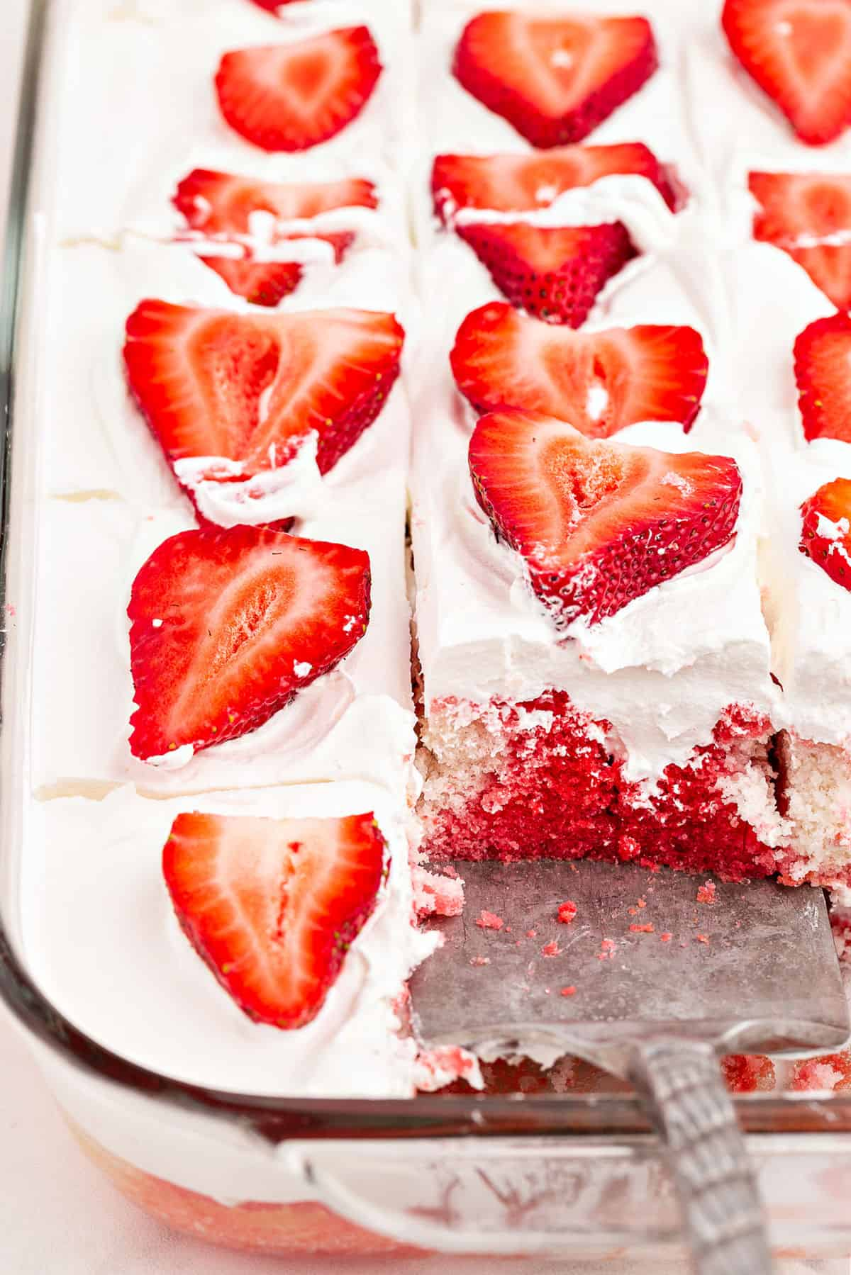 Clear glass baking dish with strawberry poke cake and one slice removed.