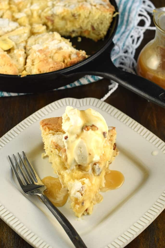 Slice of butter pecan apple cake on a white plate and topped with ice cream.