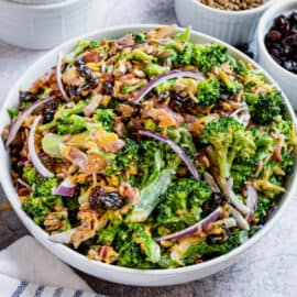 Broccoli salad with creamy dressing in a white serving bowl.