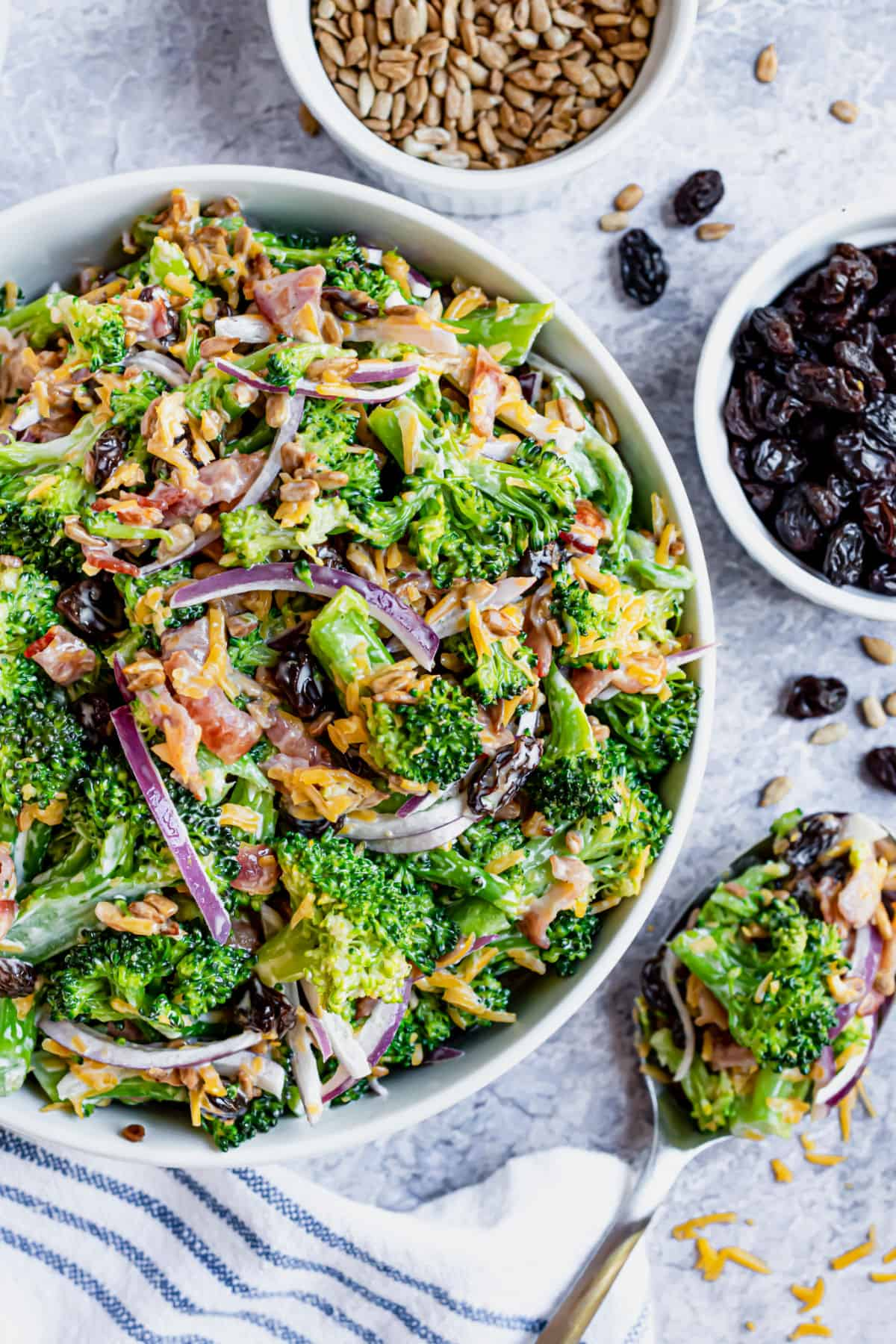 Broccoli salad in serving bowl with side of raisins and sunflower seeds.