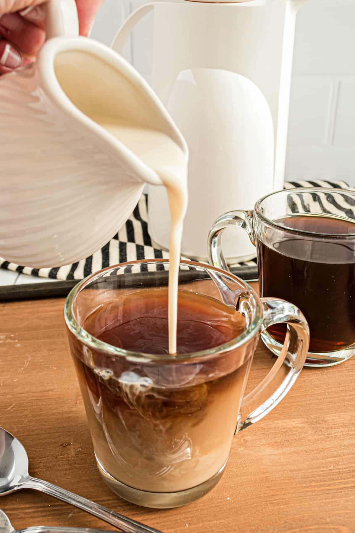 Clear mug of coffee with pitcher of coffee creamer being added to coffee.