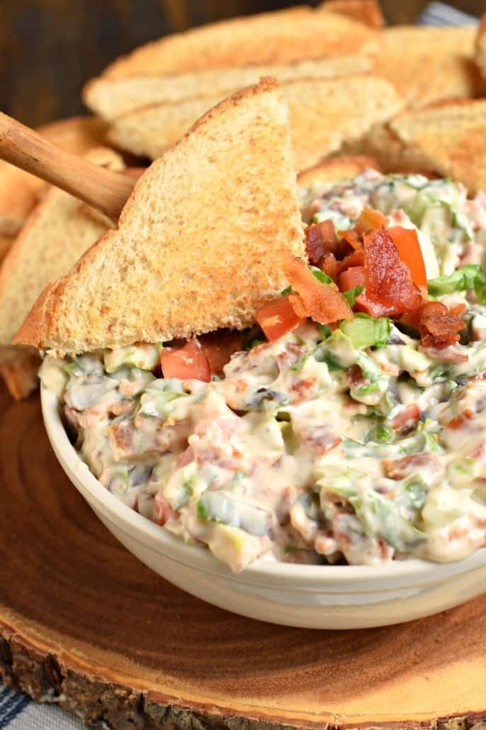 Bacon lettuce and tomato dip in a white bowl with triangles of toast to scoop and serve.