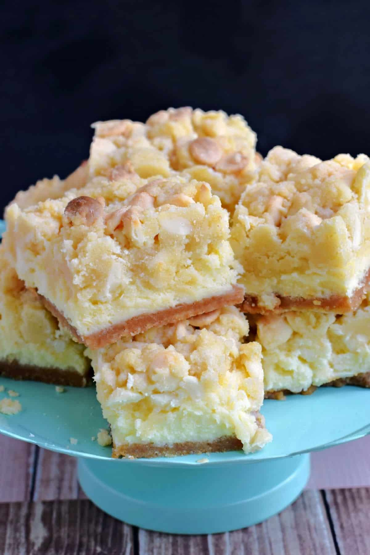 Squares of lemon cheesecake cookie bars on a teal cake platter.