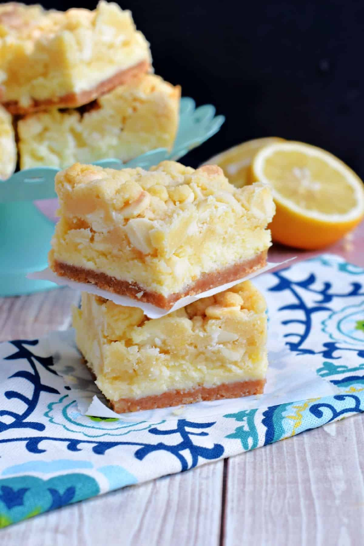 Two lemon cheesecake cookie bars stacked on top of eachother.