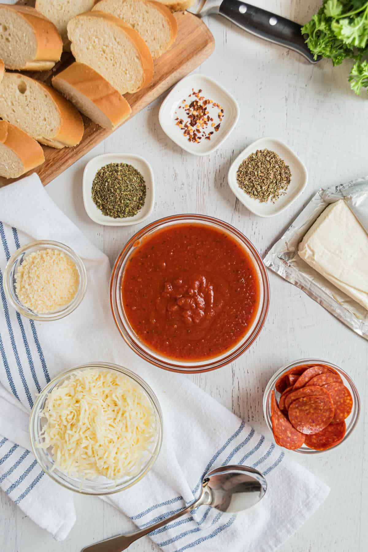 Ingredients needed for pepperoni pizza dip, including cream cheese, pizza sauce, pepperoni, and cheese.