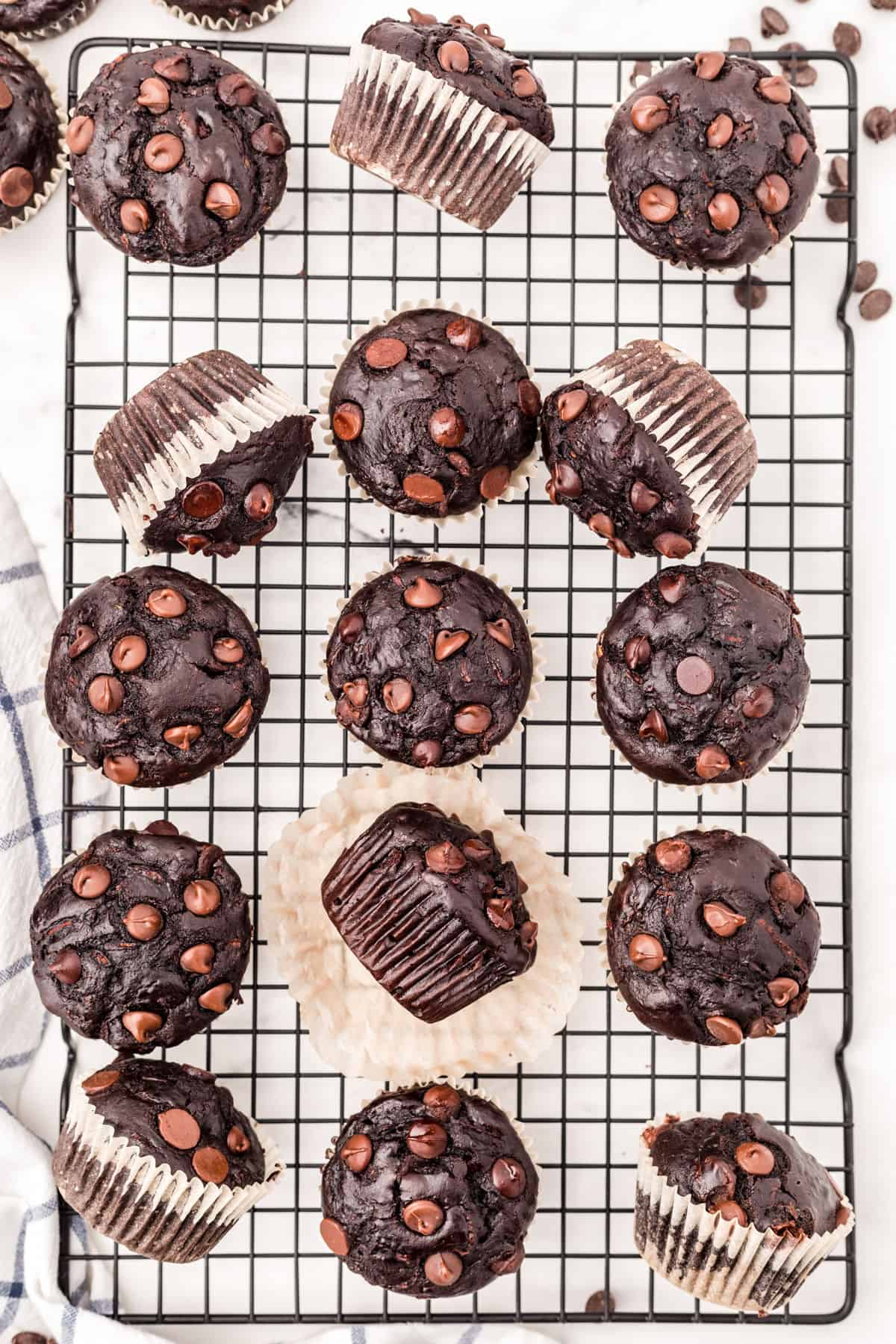 Zucchini muffins with chocolate on a wire cooling rack.