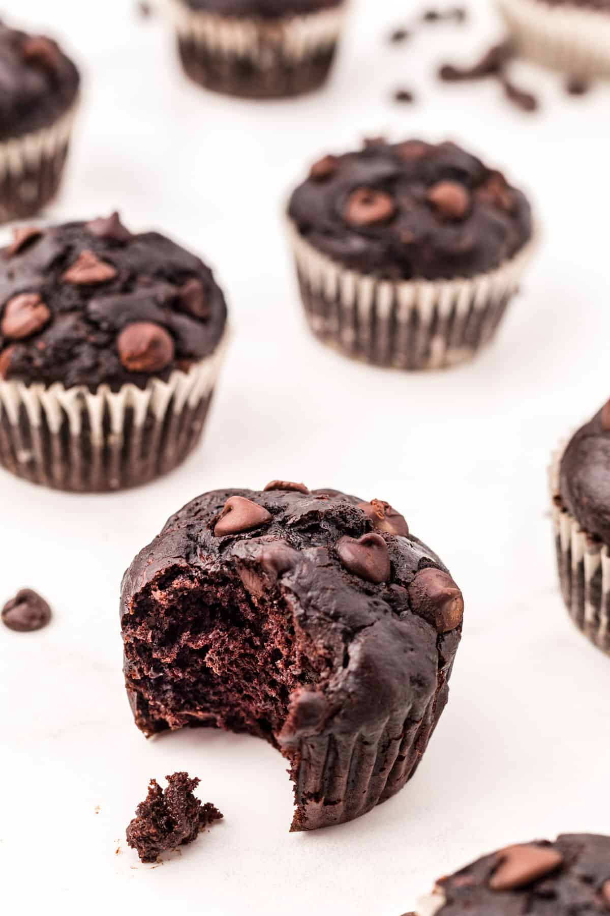 Chocolate zucchini muffins with one bite removed.