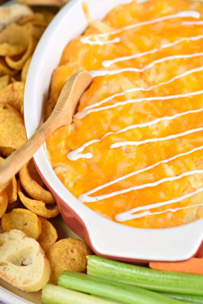 Easy Buffalo Chicken Dip in oval dish served with baguettes, fritos, carrots, and celery.