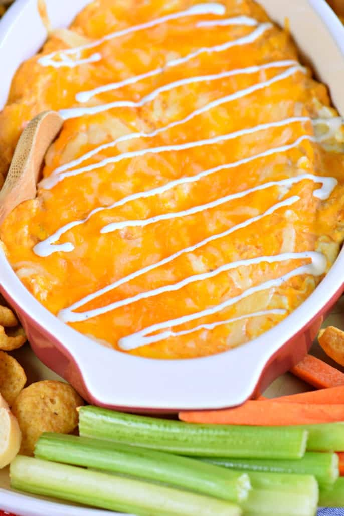 Buffalo chicken dip in oval baking dish topped with melted cheese and blue cheese drizzle.