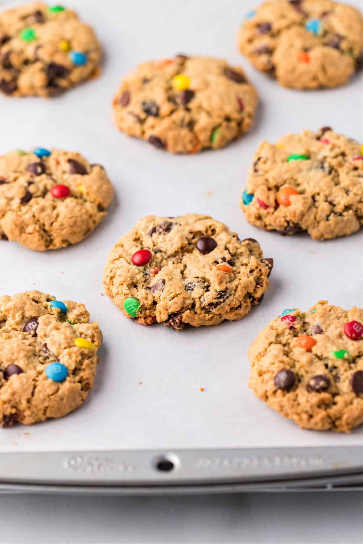 Monster cookies baked on a parchment paper lined cookie sheet.