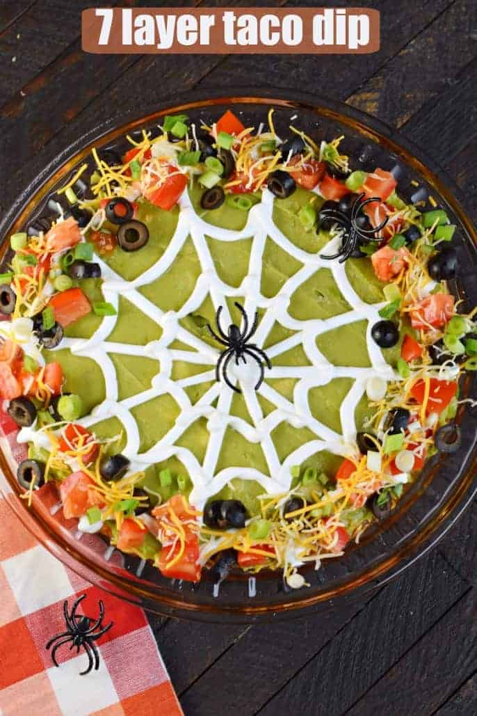 Halloween seven layer taco dip decorated with spider web made from sour cream.