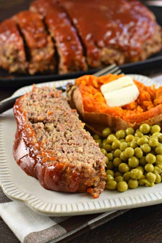 Slice of glazed meatloaf on a white plate with a side of sweet peas and sweet potato.