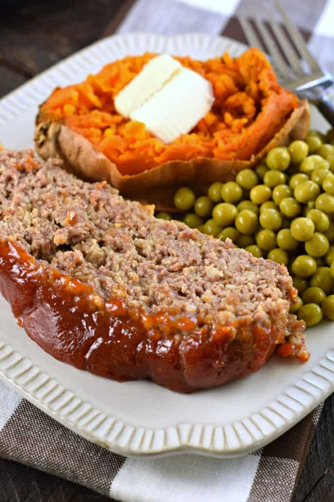 Slice of bbq glazed meatloaf on a dinner plate with sweet potato and peas.