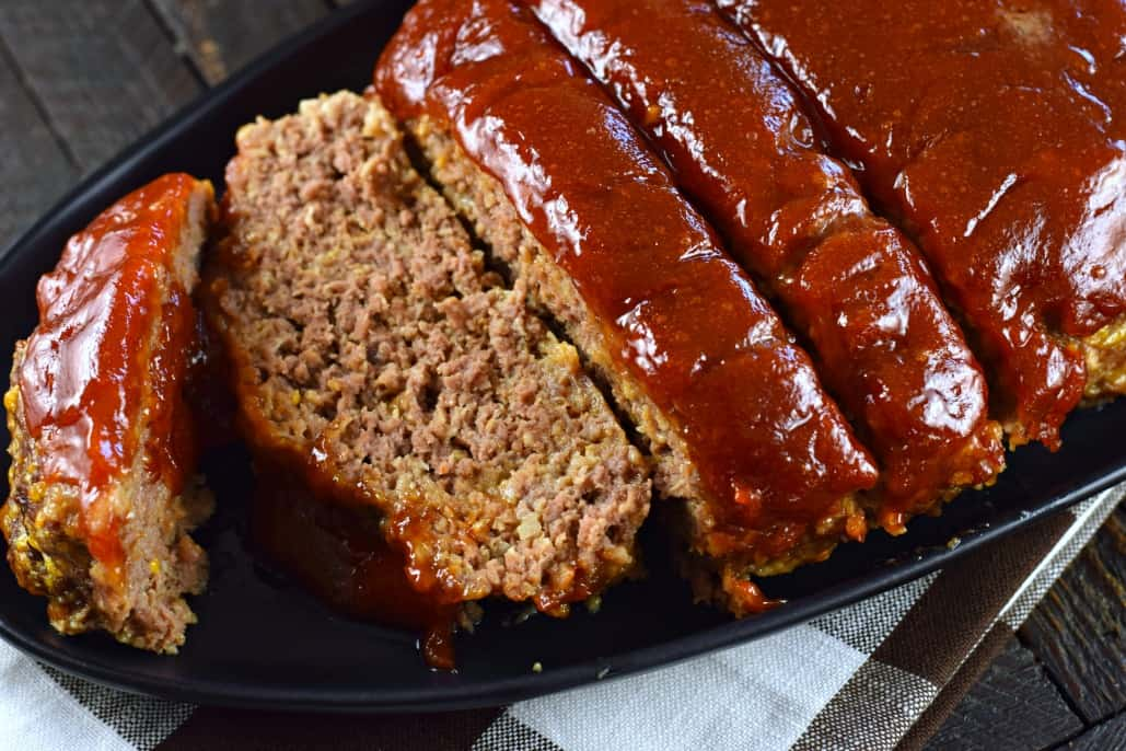 Meatloaf on a black plate, sliced for serving.