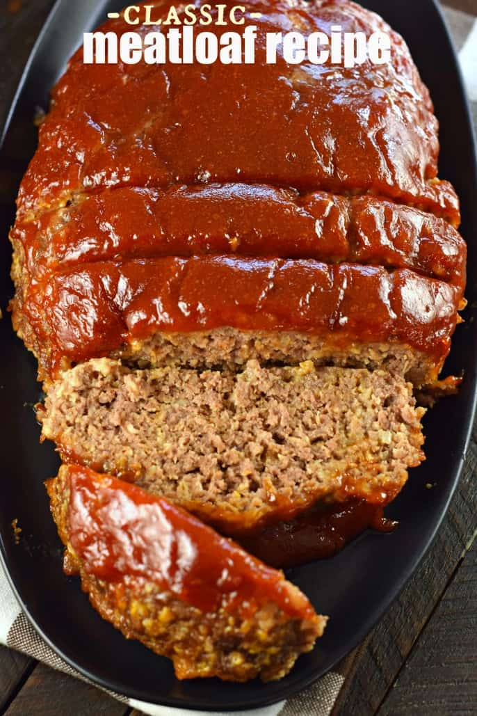 While meatloaf on a black plate, sliced and topped with a tangy bbq glaze.