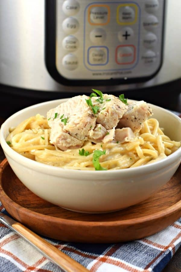 Instant Pot with bowl of creamy Chicken Alfredo and parsley garnish