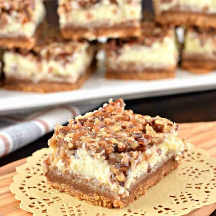 The layers on these Pecan Pie Cheesecake Bars are incredible! One tasty bite and you'll fall in love! From the graham cracker crust, to the sweet cheesecake filling and the pecan pie topping, this holiday dessert receives rave reviews from everyone!