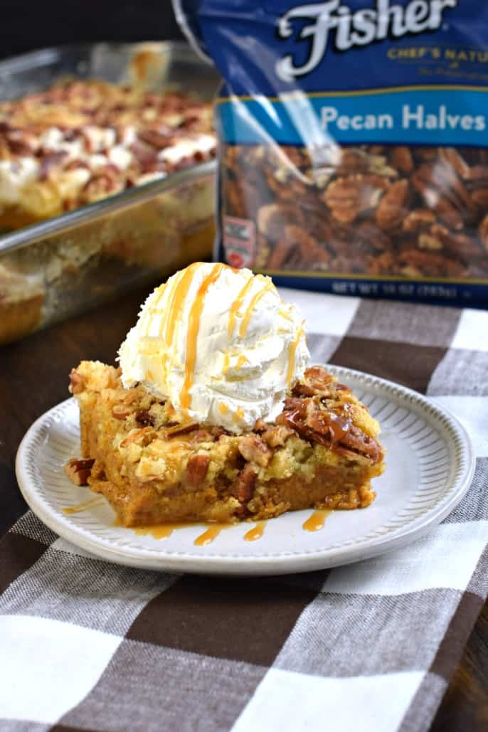 Pumpkin Dump Cake recipe served with whipped cream and caramel