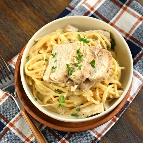 Bowl of fettuccine alfredo topped with chicken and parsley. Served on a plaid napkin and a fork