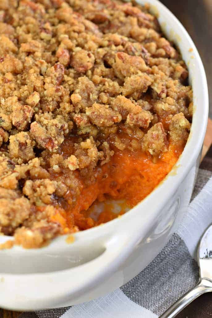 White baking dish with mashed sweet potato casserole and crunchy streusel topping. one scoop missing.