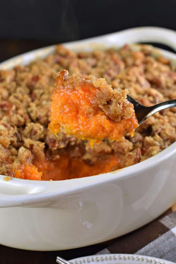 Big spoonful of mashed sweet potato casserole from a white baking dish.