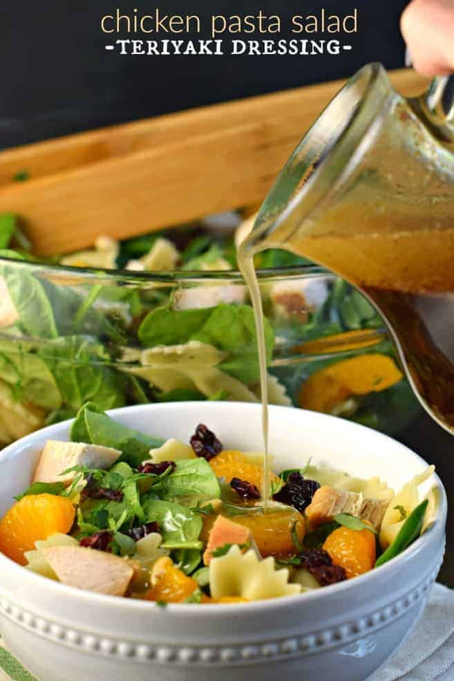 White salad bowl with spinach and pasta with chicken, mandarin oranges, and dressing being drizzled over the top.