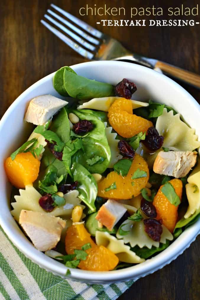 White salad bowl with chicken pasta salad and mandarin oranges.